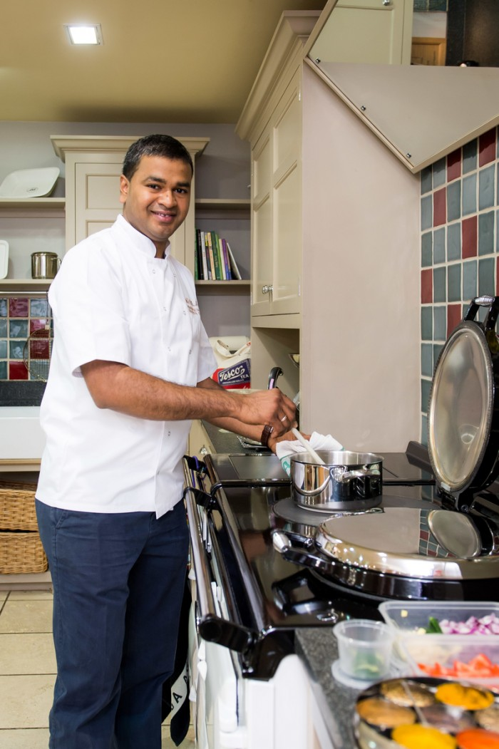 Praveen Kumar pulls on his cook demo apron and prepares to show us how the great British Classic handles his Indian Cuisine.