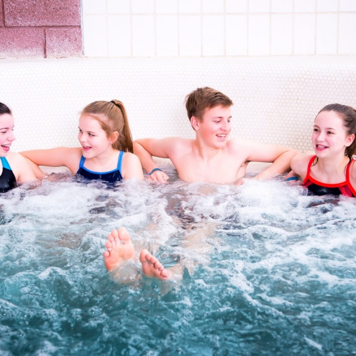 Teenagers having a gossip in the huge Jacuzzi bath at the Leisure Pool.