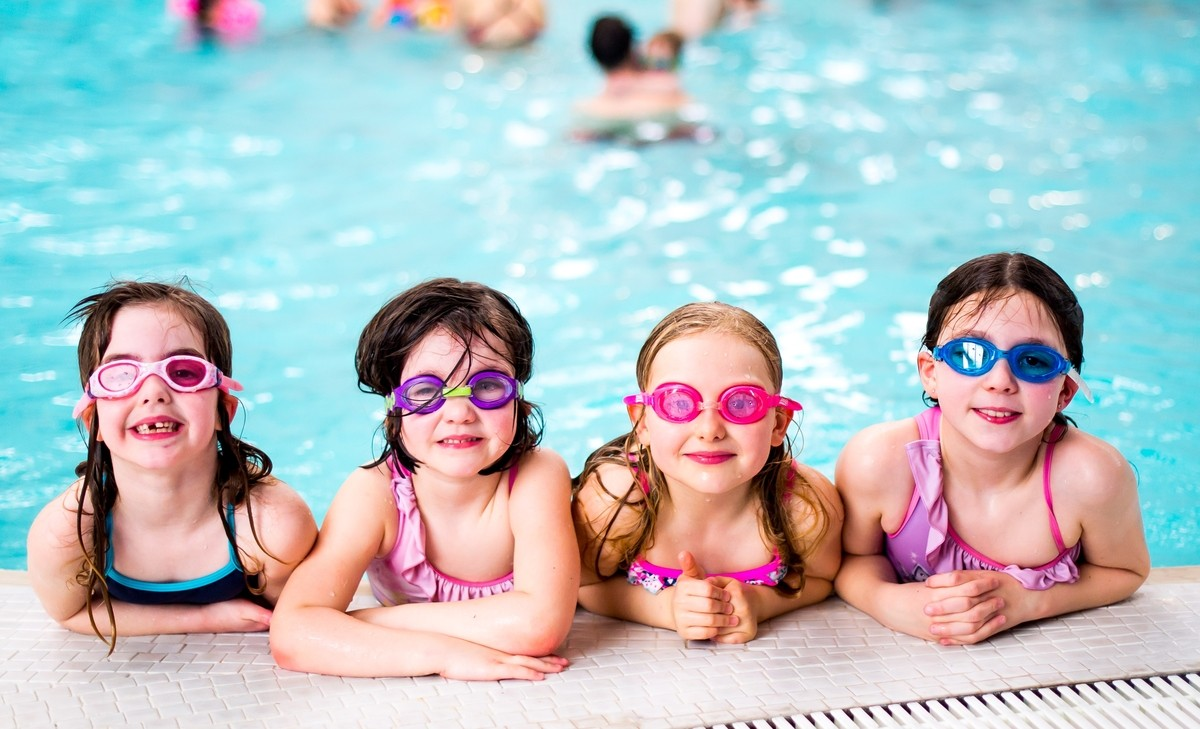 Swim and Skate - girls with goggles at the edge of the pool.