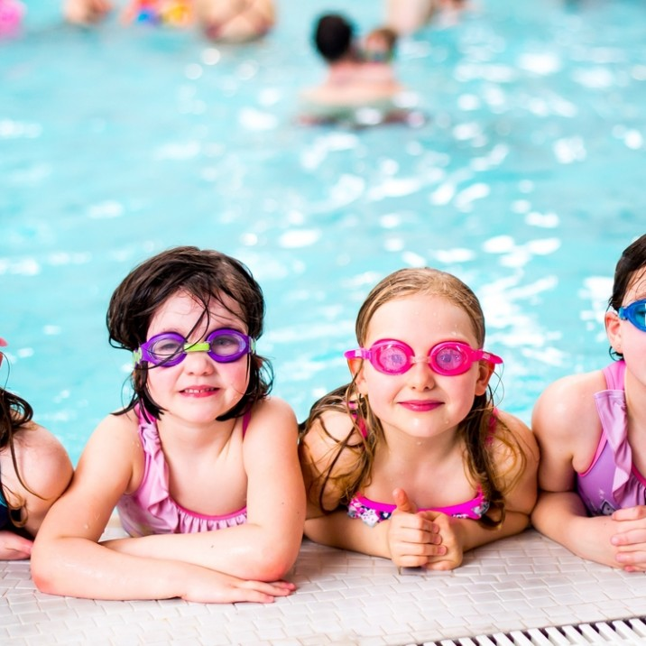 Girls with their goggles on having a break from all the fun at the edge of the pool.