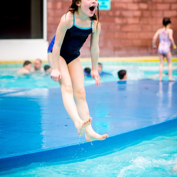 Girl jumping into the outdoor pool.