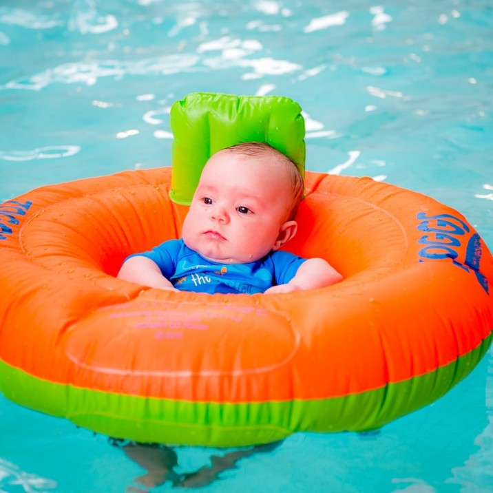 Baby in inflatable ring in the pool.
