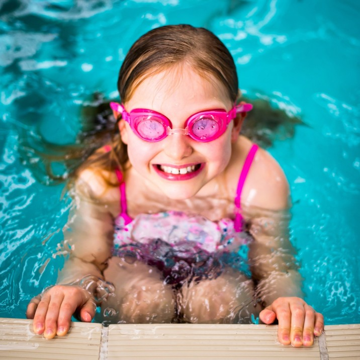 Girl with goggles on at the side of the pool.