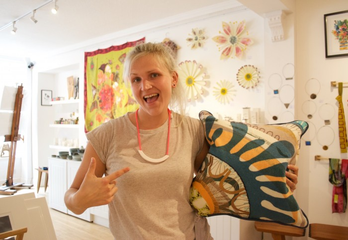 Tayberry Gallery in Perth UK is packed with the best of British, handmade art and design. Tayberry Gallery has been on Princes Street for 7 years, and showcases the work of lots of local creatives. Pictured is Louise (one half of Tayberry) loving the new cushions by Kelly Mackay inspired by Scottish geology, and Beth Lamont's colourful ceramic necklace!