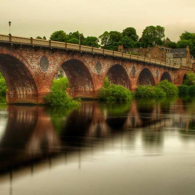 The Old Bridge spanning over the River Tay. The water is so still it shows as a mirrored image reflected in the silvery water.