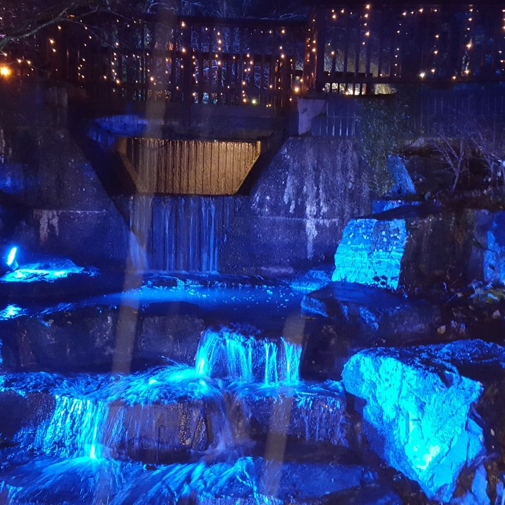 The waterfall takes on a mystical air, as coloured lights dance across the surface.