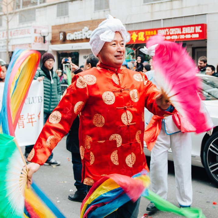 Man dancing with rainbow coloured ribbons as part of New York's Chinese New Year street party.