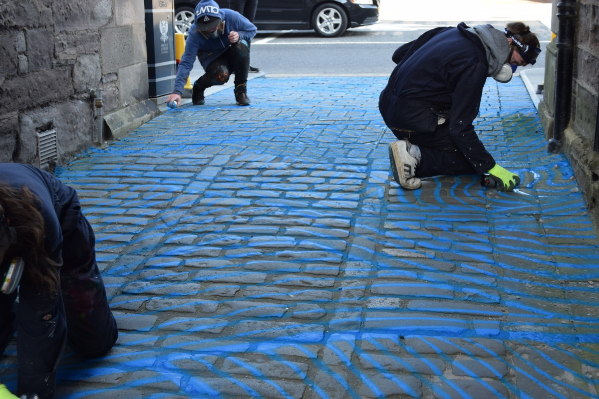 Vennels Guerilla Art Project Water Vennel painting the cobbles blue!