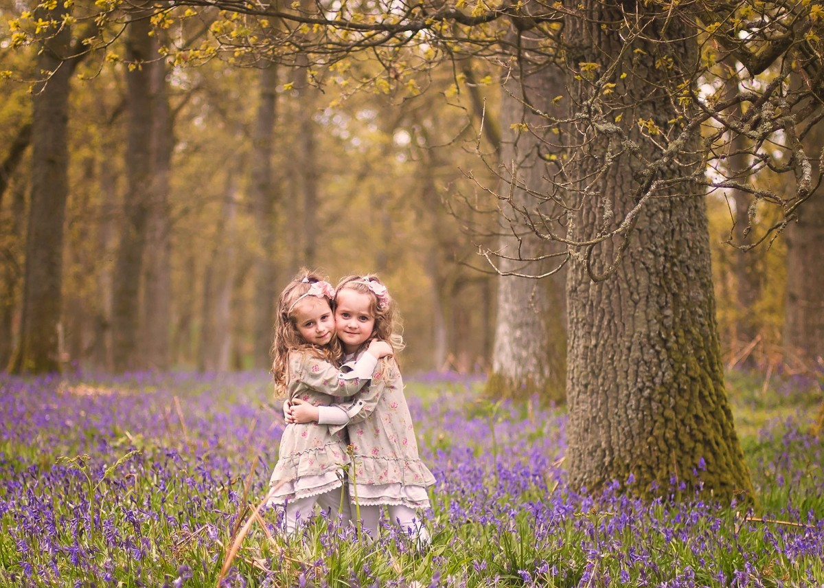 Girls sharing a cuddle with the bluebells in the background!