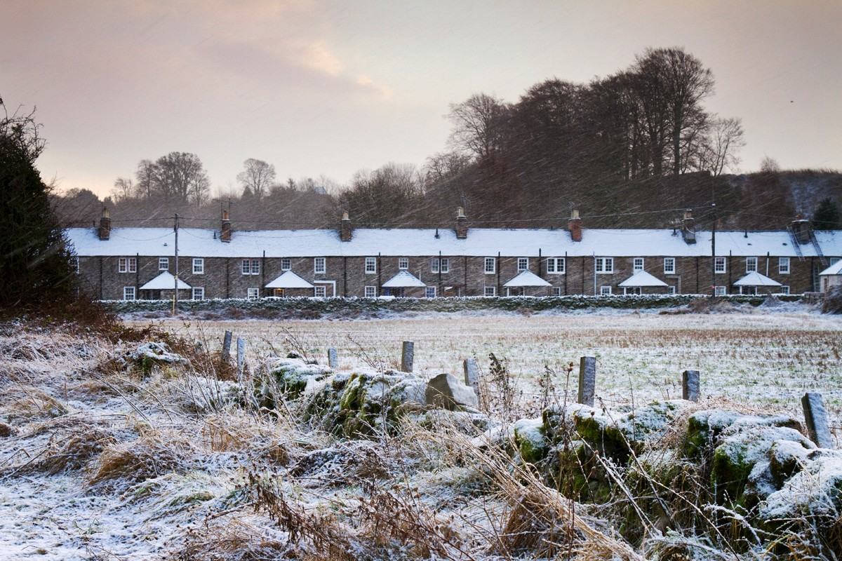 The first frost sets over a row of farmers cottages