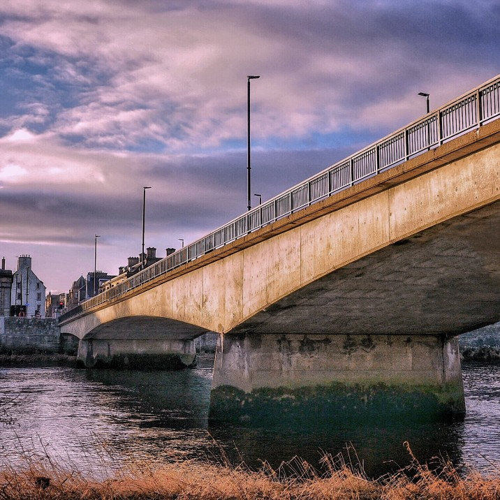Perth's Queens Bridge looking towards Tay Street. Photo taken from below bridge at the edge of the River Tay looking up
