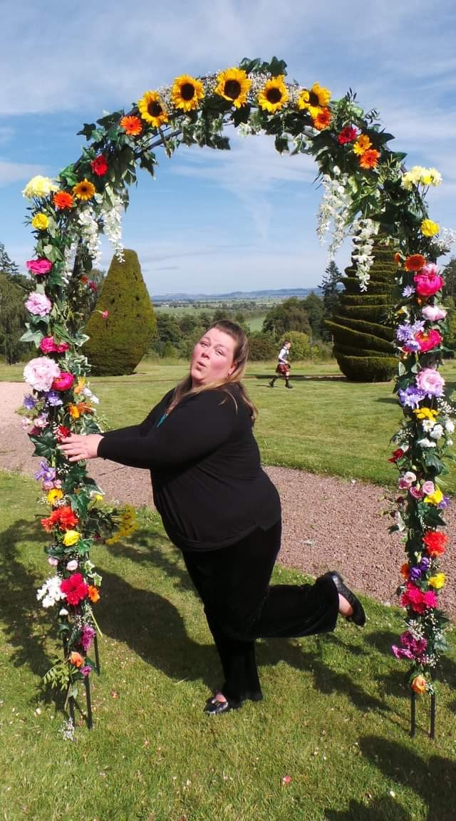 Jan shows her hilarious personality while pouting under a floral ceremonial arch in the grounds of Fingask