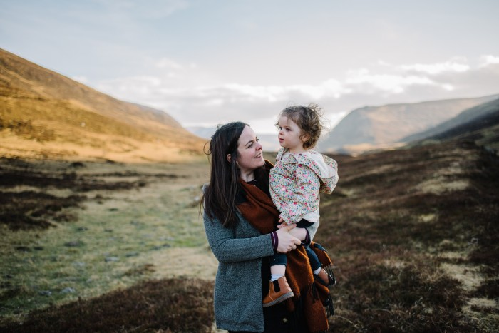 Wedding photographer Ruth Segaud stands in Highland Perthshire holding her baby daughter.