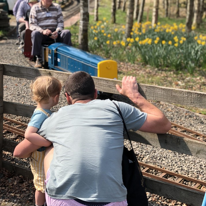 A little boy and his daddy peep through the fence to watch the oncoming train at Wester Pickston Railway, Methven, Perthshire