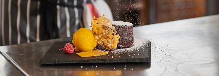 Study Food studies and Hospitality at Perth College UHI. This shows a delicious chocolate souffle with a honeycomb crisp, raspberry and a yellow coloured fruit sorbet served on a slate and being sprinkled with white icing sugar.