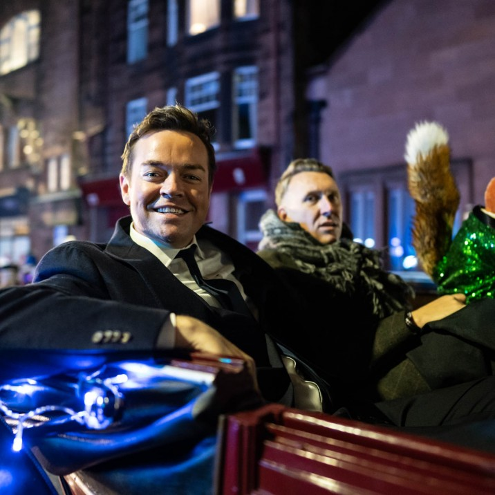 Stephen Mulhern and Basil Brush riding in style in a horse drawn carriage.